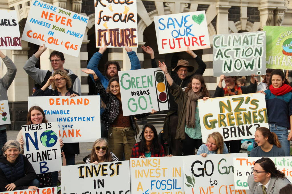 350 Dunedin hold signs that read 'Green means Go', 'Ensure your bank never invest your money in coal, oil, and gas', 'NZ's Greenest Bank?', 'Banks invest in a fossil free future'. 'demand a sustainable investment from your bank'